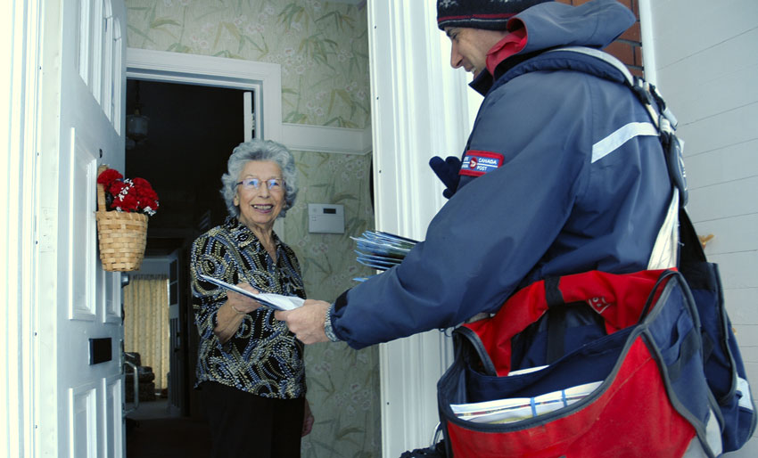 Letter carrier delivers mail to the door of a smiling senior woman